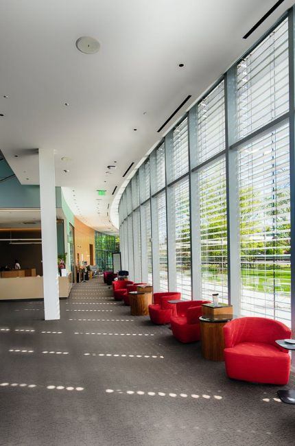 Na korytarzu stoją czerwone meble. Po prawej stronie są okna. Sposób na to jak myć okna znajduje się w tekście.