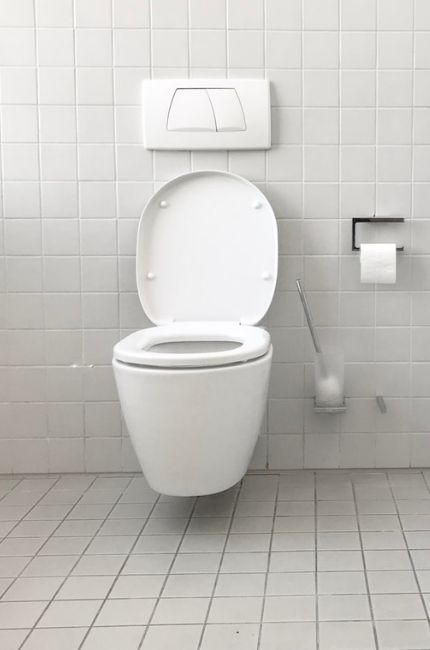 Na środku ściany w łazience znajduje się toaleta. Toaleta ma zapchany odpływ. Powyzej znajduje się spłuczka a po boku papier toaletowy.