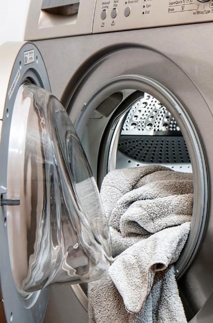 Pralka z włożonym ręcznikiem. Przygotowanie do prania