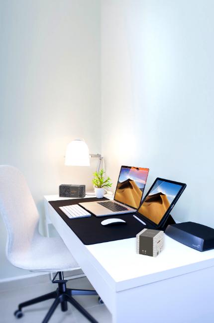 Na biurku położone są dwa pudełka, w których znajdują się chusteczki higieniczne. W tle obrazka są laptop i krzesło obrotowe.