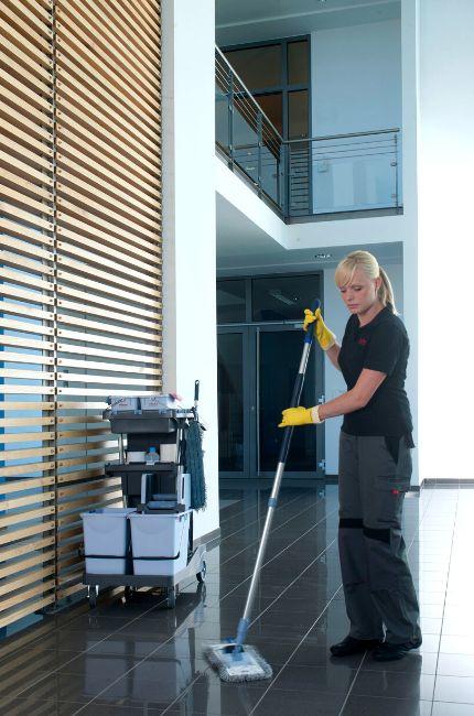 W korytarzu stoi osoba sprzątająca mopem podłogę. Kobieta używa wózek do sprzątania.