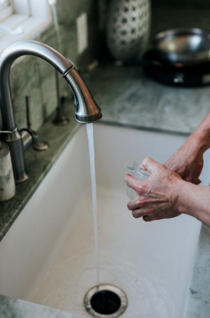 Osoba myje naczynia płynem do naczyń.